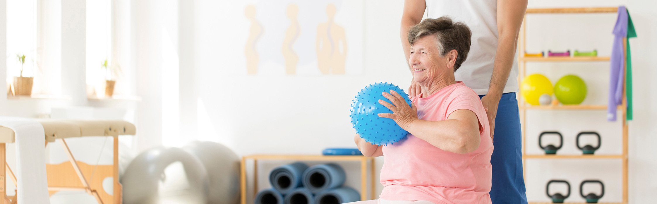 elderly lady holding a ball exercising with pink top on in a home gym