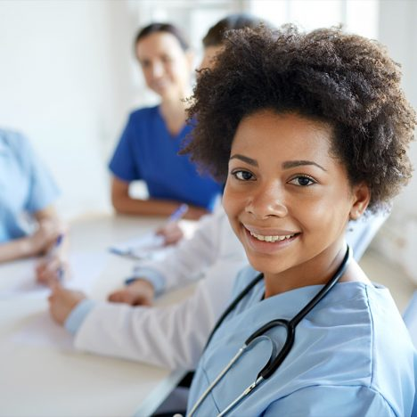 Female doctor smiling at camera with blue shirt on and stethoscope