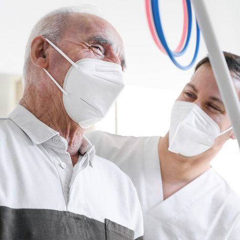 2 men smiling with masks on whil in consult