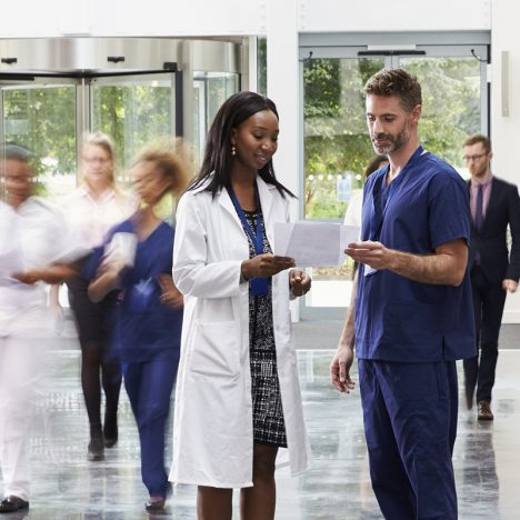 Doctors standing in room with people walking past them