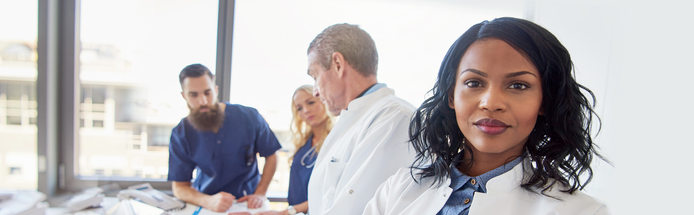 Picture of people wearing white coats with blue in the back
